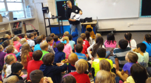 Author Cary Robinson reads his Children's Book - Monsters In My Yard - to a classroom